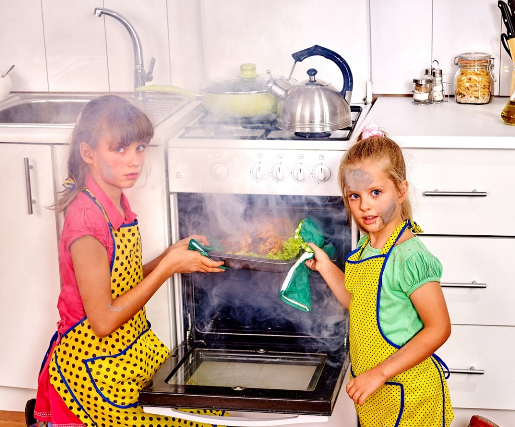 Children with a burnt cooking chicken in the kitchen. Smoke. Fac